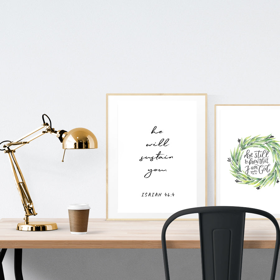 A3 beautiful calligraphy poster placed standing next to a smaller A4 sized calligraphy poster on a wooden table. Modern home interior design ideas. Minimalistic home decor.