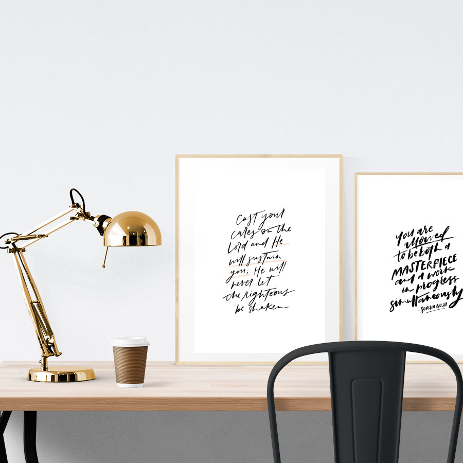 A3 calligraphy poster placed standing next to a smaller A4 sized calligraphy poster on a wooden table.