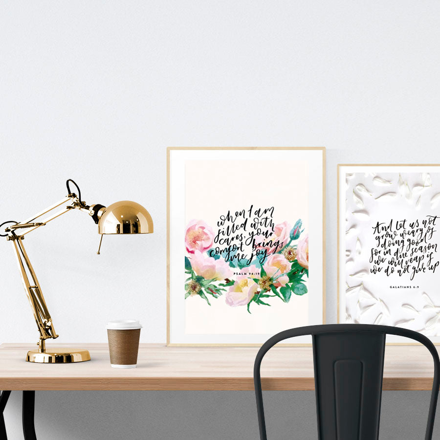A3 beautiful calligraphy poster placed standing next to a smaller A4 sized calligraphy poster on a wooden table. Minimalistic Christian home interior design ideas.
