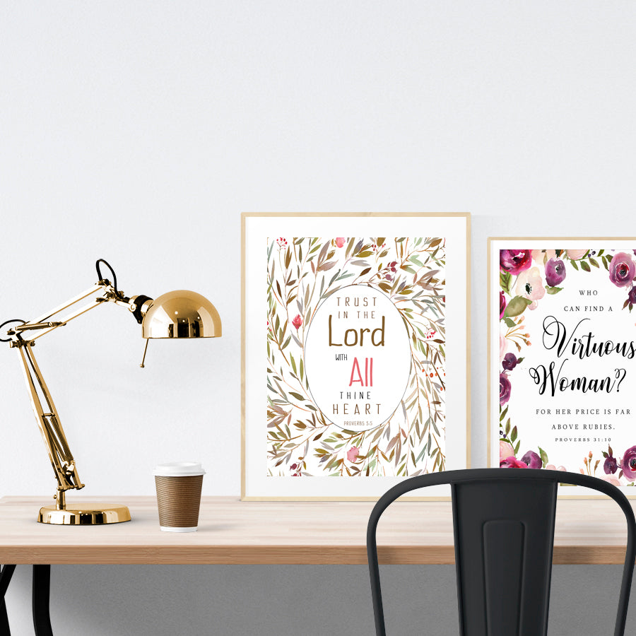 Potrait poster featuring flowers and bible verses from Proverbs 3:5 is placed standing on a table in a gold photo frame.