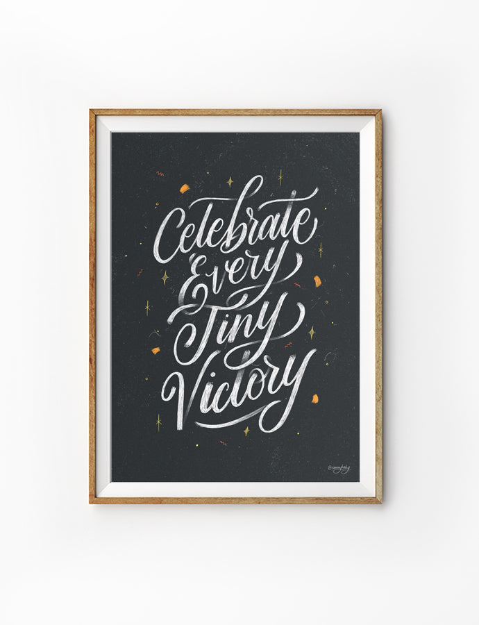 Poster featuring typography of inspirational verse 'Celebrate every tiny victory' white font on black background with confetti and sparkles details. Hung on the wall in a gold photo frame. 200GSM paper, available in A3,A4 size.