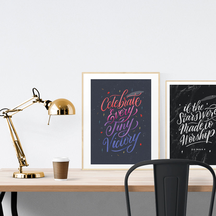 A3 calligraphy poster placed standing next to a smaller A4 sized calligraphy poster on a wooden table. Inspiring home decor ideas.