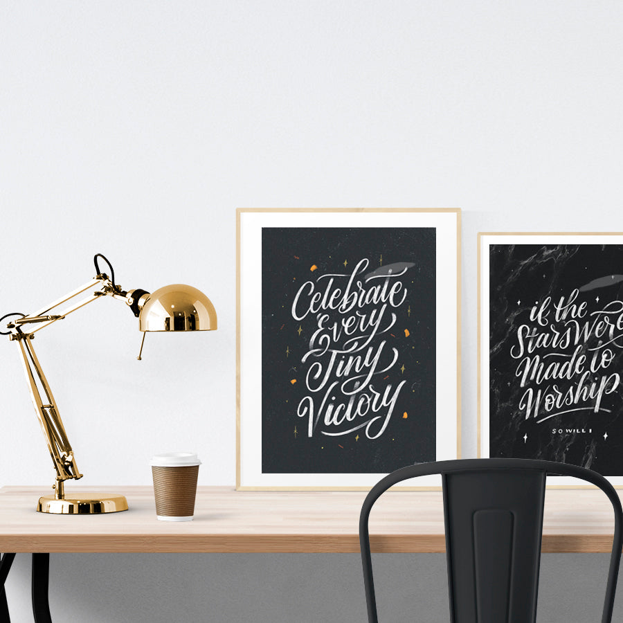 A3 calligraphy poster placed standing next to a smaller A4 sized calligraphy poster on a wooden table. Inspiring home décor ideas.