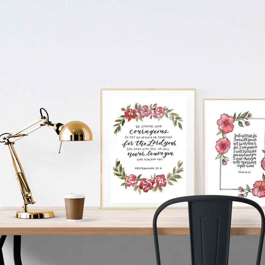 A3 Poster featuring flowers, wreath and bible verses from Joshua 1:9 is hung on the wall in a gold photo frame stood on a wooden table next to a smaller A4 poster with flower designs.