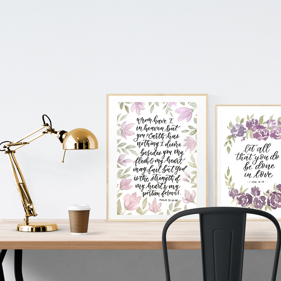 A3 beautiful calligraphy poster placed standing next to a smaller A4 sized calligraphy poster on a wooden table. Rustic Christian home interior design ideas.