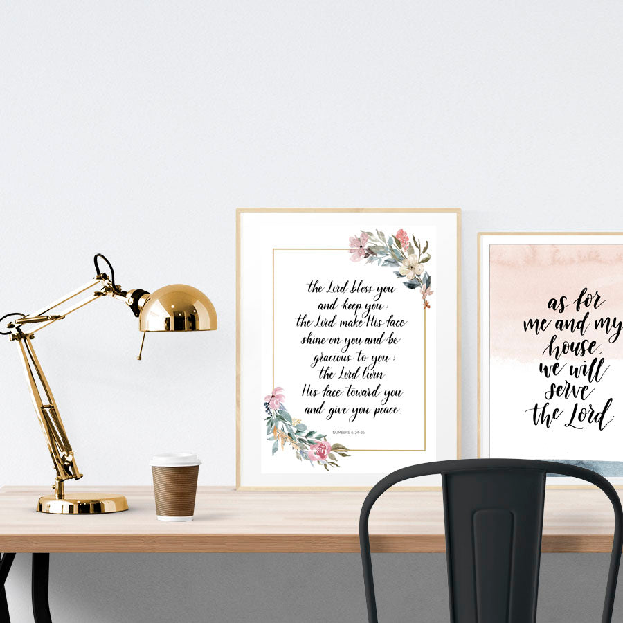A3 Poster featuring typography of Numbers 6:24 is displayed in a gold frame standing on a wooden table next to a smaller A4 poster with blush pink and white theme. Beautiful creative home décor ideas.