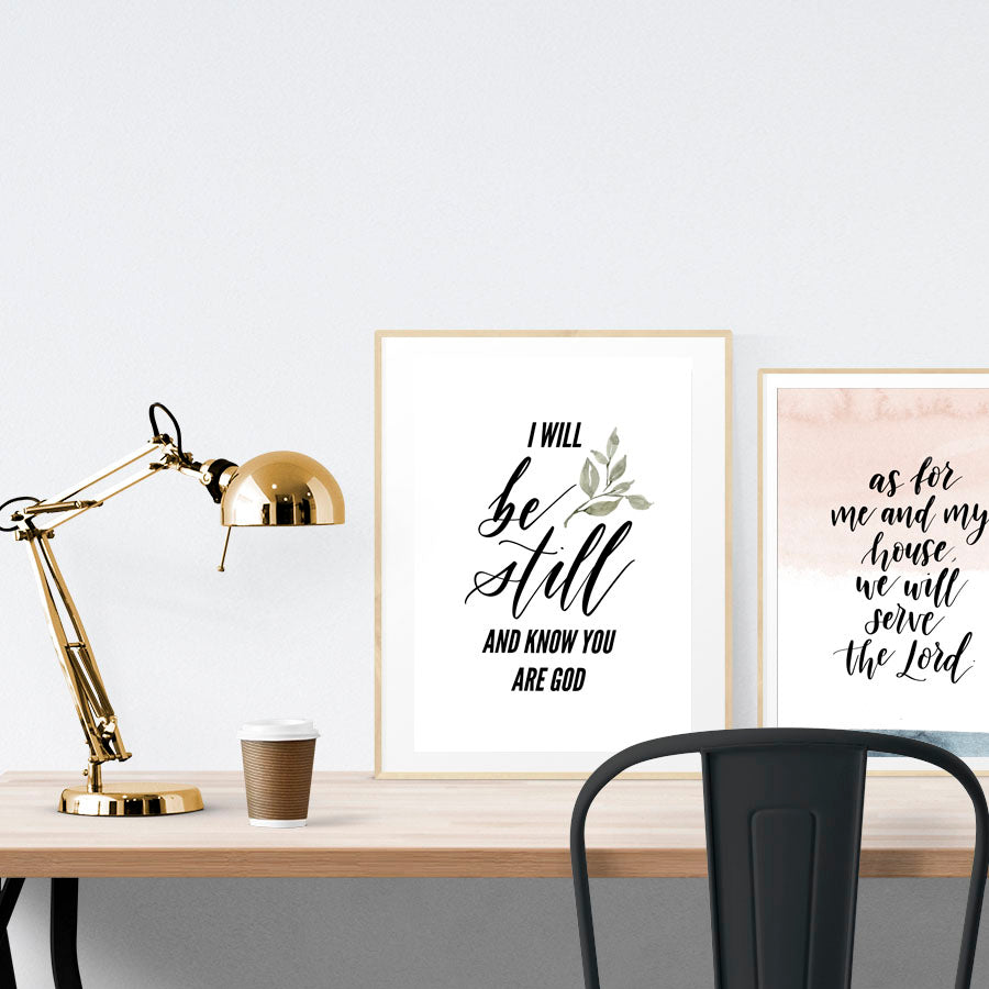 A3 Poster featuring typography of Psalm 46:10 is displayed in a gold frame standing on a wooden table next to a smaller A4 poster with blush pink and white theme.