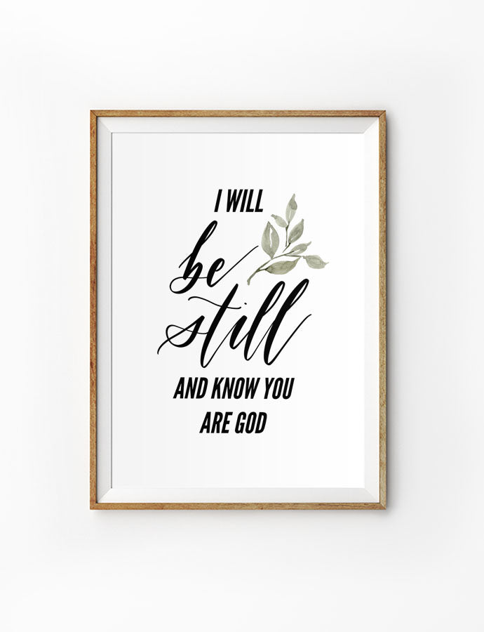 Poster featuring a sprig and bible verses from Psalm 46:10 is hung on the wall in a gold photo frame.