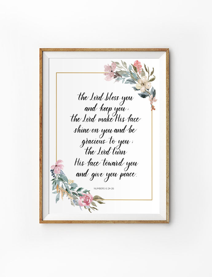 Poster featuring flowers and bible verses from Numbers 6:24 is hung on the wall in a gold photo frame.