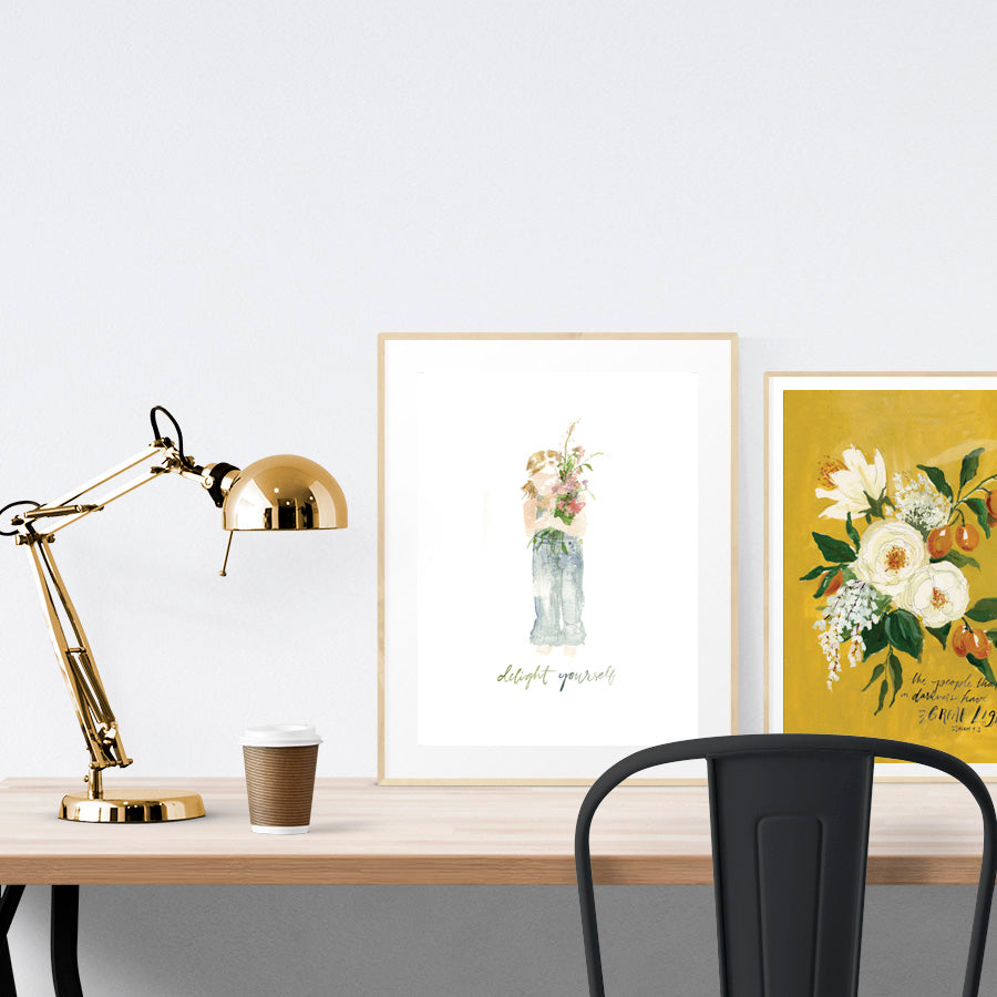 A3 calligraphy poster with girl and flowers theme placed standing next to a smaller A4 sized calligraphy poster with yellow flowers theme on a wooden table. Inspiring home decor ideas.