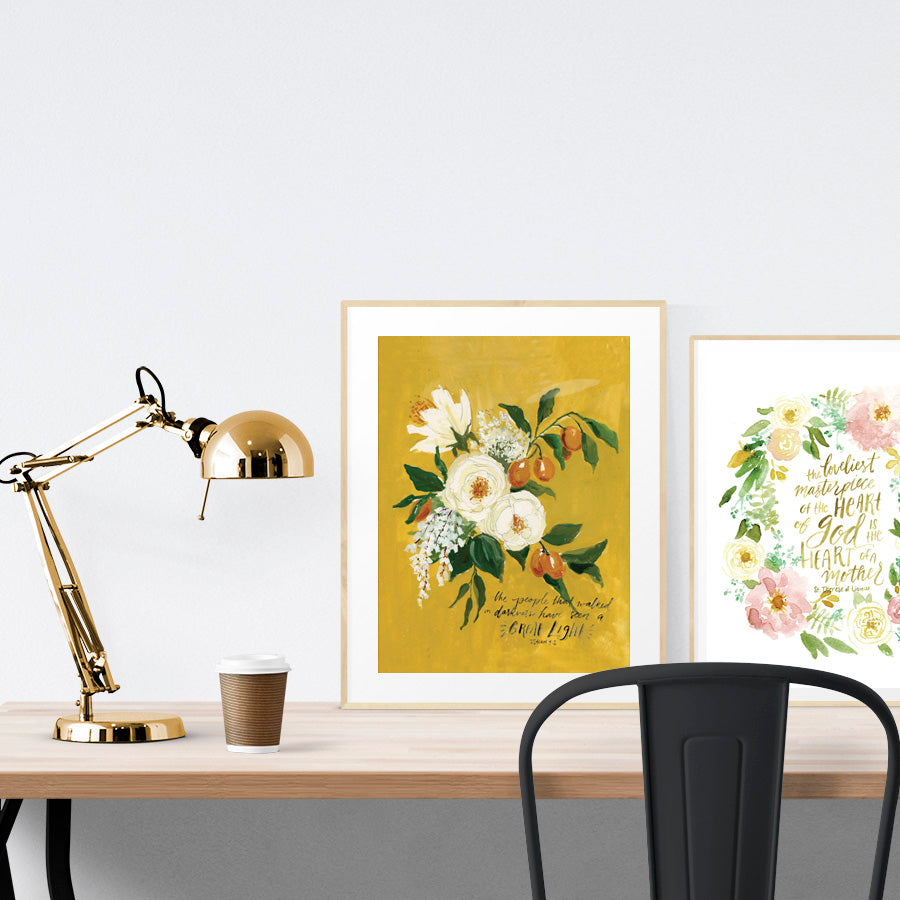 A3 beautiful painting poster placed standing next to a smaller A4 sized floral calligraphy poster on a wooden table. Inspiring home decor ideas.