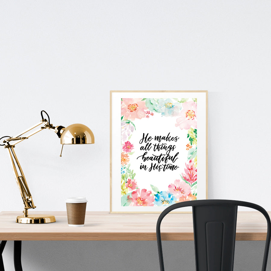 Poster featuring flowers and bible verses from Ecclesiastes 3:11 is placed standing on a brown table in a gold photo frame.