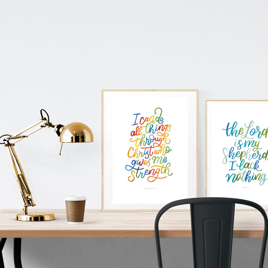 A3 calligraphy poster with colourful theme placed standing next to a smaller A4 sized calligraphy poster with shades of blue theme on a wooden table. Inspiring home decor ideas.