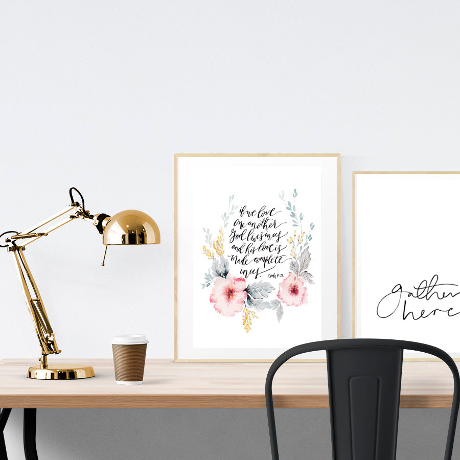 A3 beautiful flower calligraphy poster placed standing next to a smaller A4 sized calligraphy poster on a wooden table. Modern home interior design ideas.