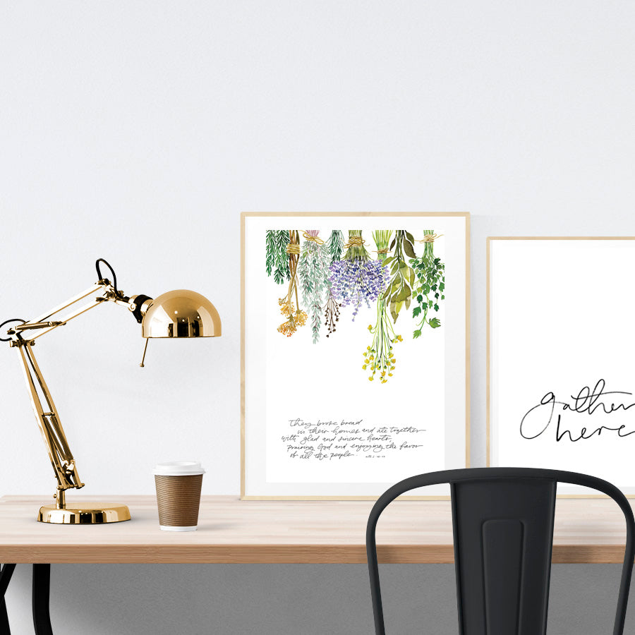 A3 beautiful calligraphy poster placed standing next to a smaller A4 sized calligraphy poster on a wooden table. Floral Christian home interior design ideas.