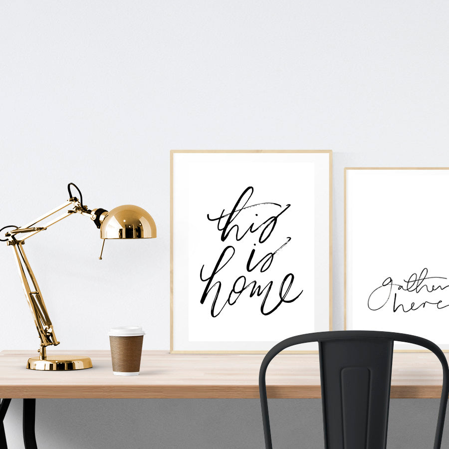 A3 beautiful calligraphy poster placed standing next to a smaller A4 sized calligraphy poster on a wooden table. Minimalistic home interior design ideas.
