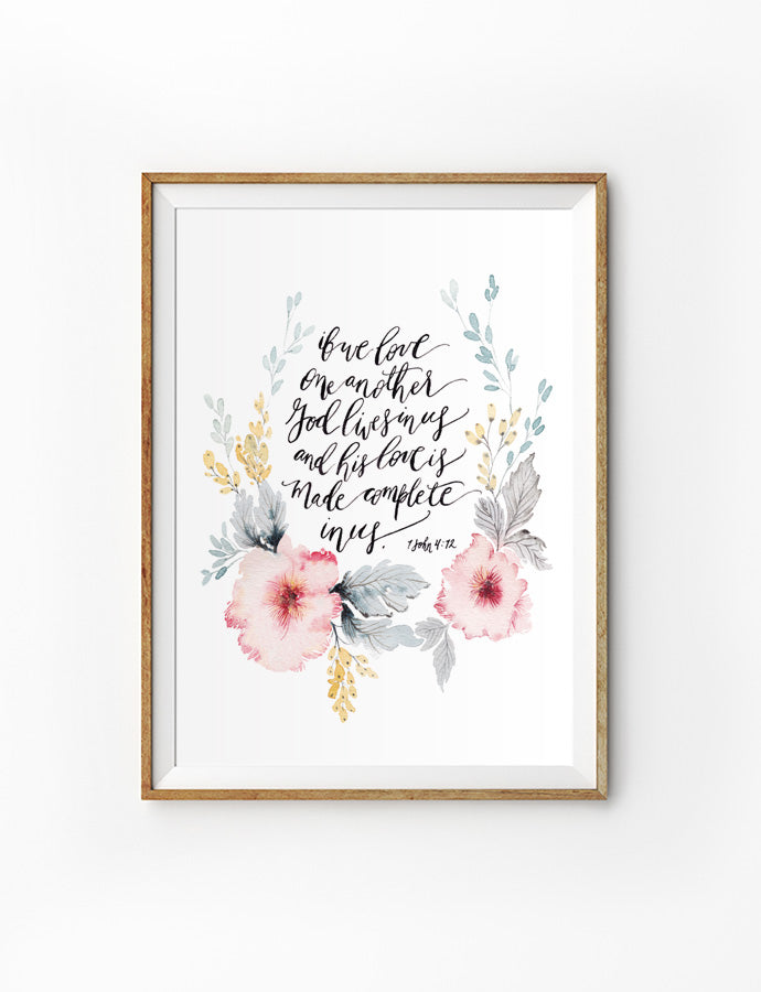 Poster featuring beautiful typography bible verses with flower wreath designs 'but love one another God lives in us and his love is made complete in us' is hung on the wall in a gold photo frame'. 200GSM paper, available in A3,A4 size.