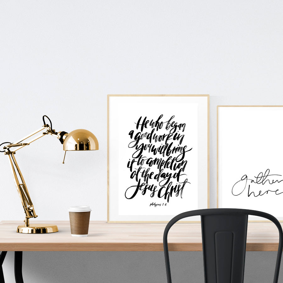 A3 beautiful calligraphy poster placed standing next to a smaller A4 sized calligraphy poster on a wooden table. Minimalistic decor, Modern home interior design ideas.