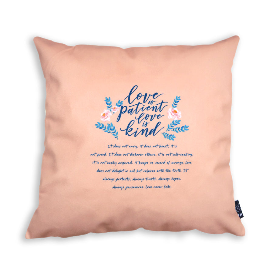 The back of the cushion cover features the background in salmon pink and the full love is patient love is kind bible verse.