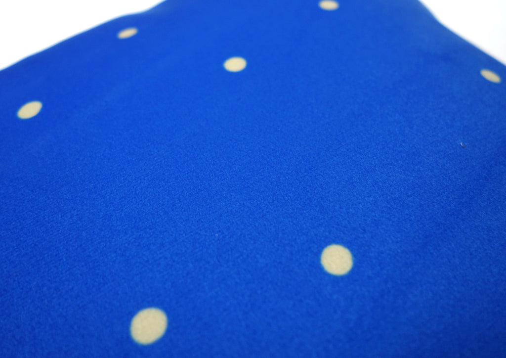 Yellow polka dot on blue background on the back of velvet soft cushion cover.