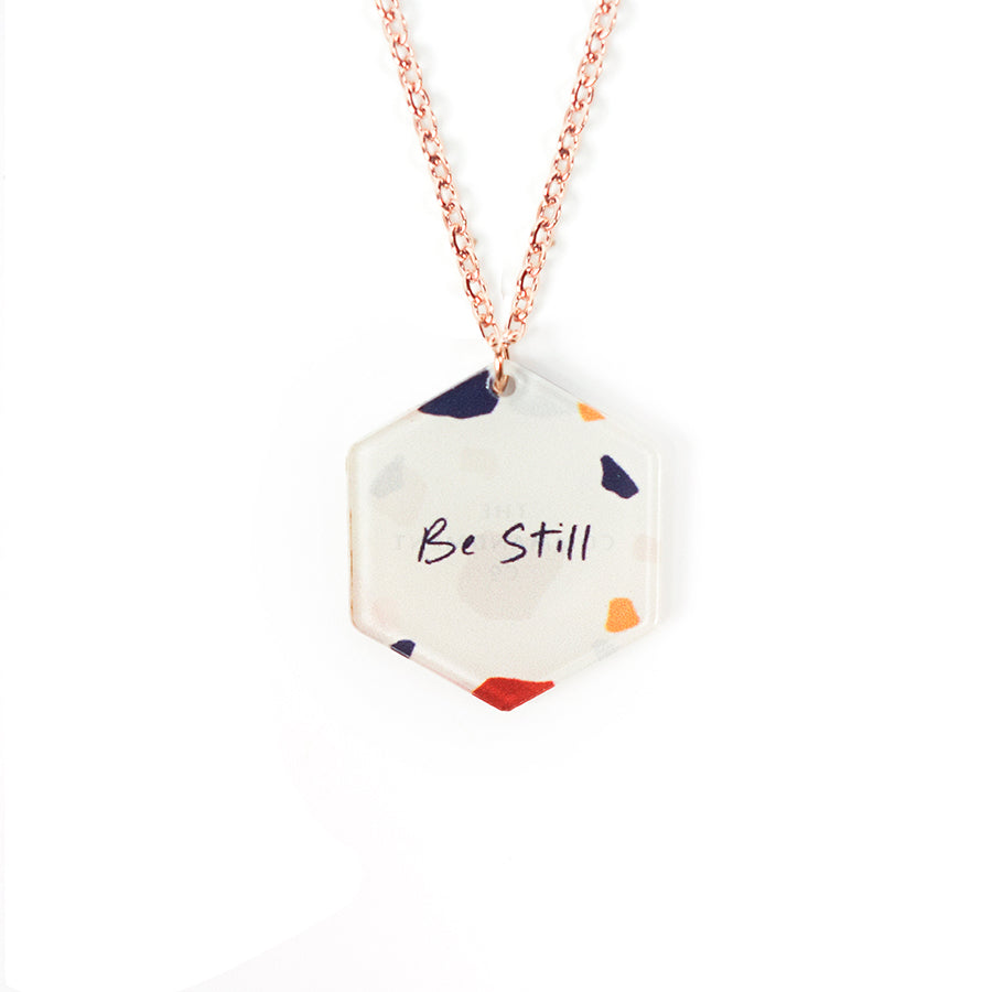 Acrylic hexagonal shaped white pendant with abstract designs and bible verse 'be still'. This necklace makes for unique gifts. Rose gold plated stainless steel chains. Pendant height 2.3cm length 2cm. Chain length 42-46.5cm.