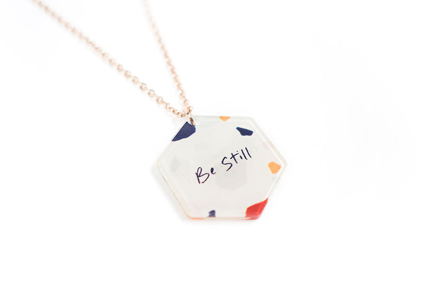 Close up of Acrylic hexagonal shaped white pendant with abstract designs and bible verse 'be still'. This necklace makes for unique gifts. Rose gold plated stainless steel chains. Pendant height 2.3cm length 2cm. Chain length 42-46.5cm.