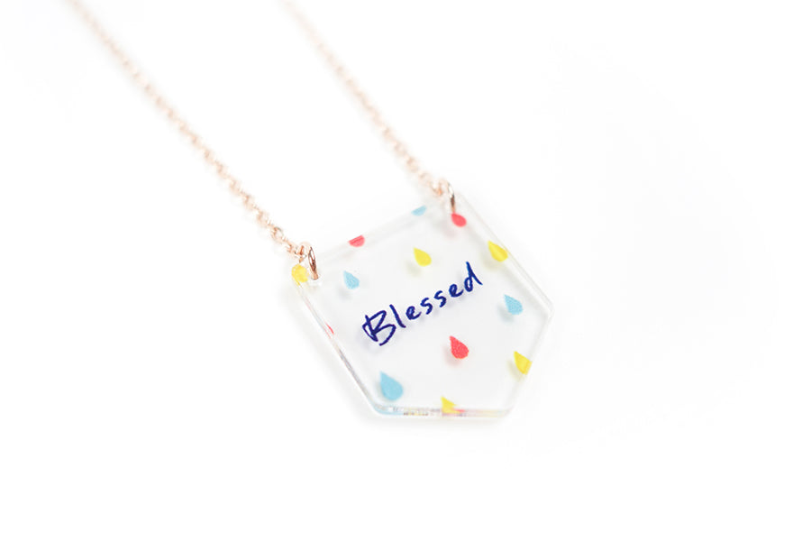 Perspective photograph of Acrylic banner shaped transparent pendant with abstract designs and bible verse 'blessed'. This necklace makes for unique gifts. Rose gold plated stainless steel chains. Pendant height 2.3cm length 2cm. Chain length 42-46.5cm.