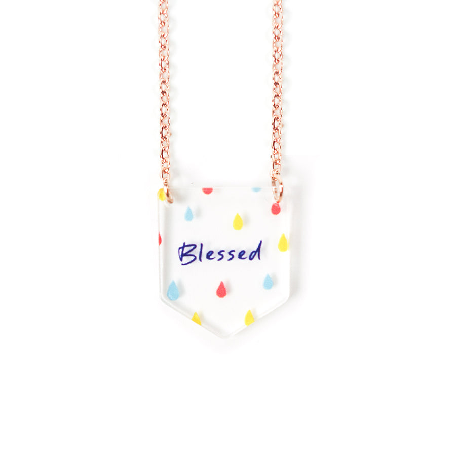 Acrylic banner shaped transparent pendant with abstract designs and bible verse 'blessed'. This necklace makes for unique gifts. Rose gold plated stainless steel chains. Pendant height 2cm length 1.7cm. Chain length 42-46.5cm.