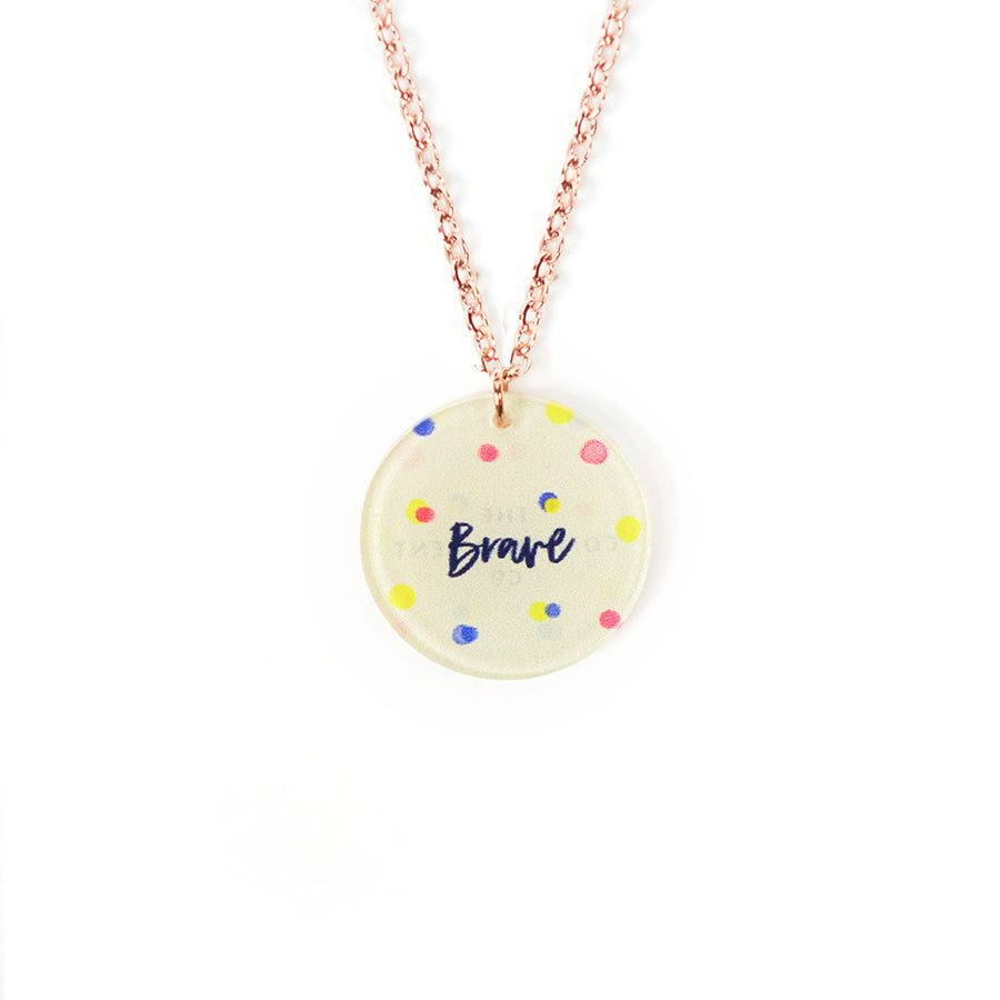 Acrylic off yellow pendant with abstract designs and encouraging verse 'Brave' makes for unique gifts. Rose gold plated stainless steel chains. Pendant diameter 1.8cm. Chain length 42-46.5cm.