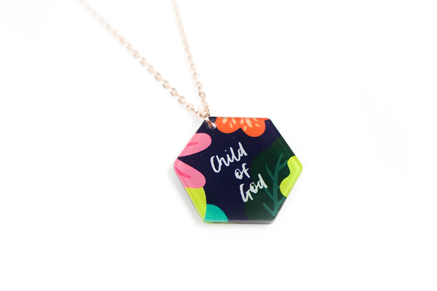 Acrylic hexagonal shaped white pendant with abstract designs and wording  'Child of God'. Rose gold plated stainless steel chains. Pendant height 2.3cm length 2cm. Chain length 42-46.5cm.