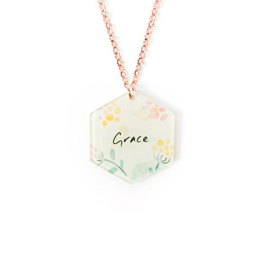 Acrylic hexagonal shaped white pendant with flower designs and wording  'Grace'. This necklace makes for unique gifts for a Christian friend or children