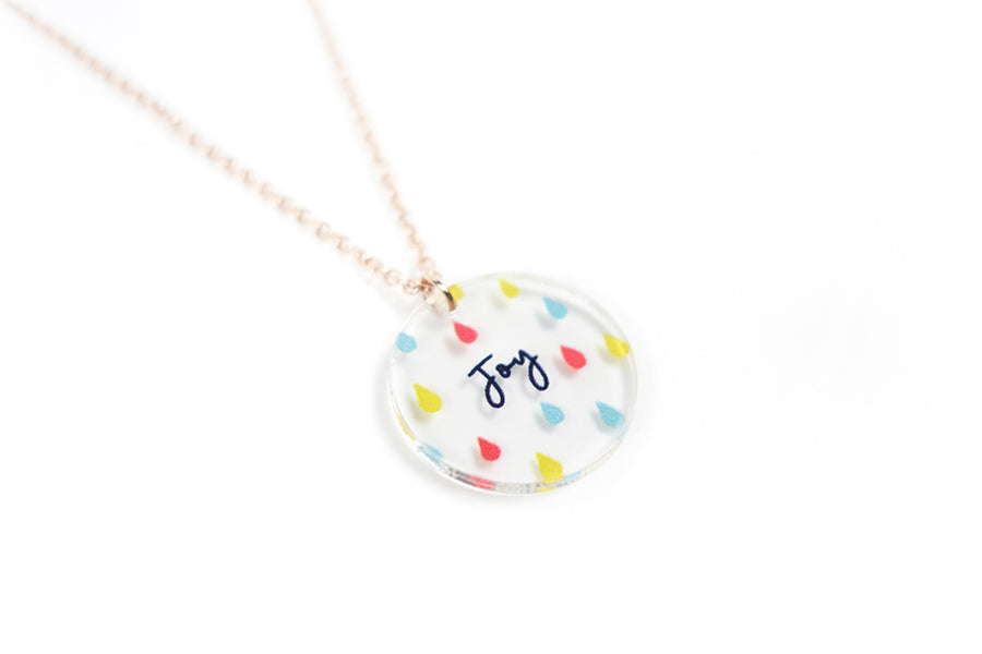 'Joy'. Acrylic round necklace with rain details. Makes for unique gifts for Christian friends. Despite the circumstances, we should always choose to have joy in our hearts.
