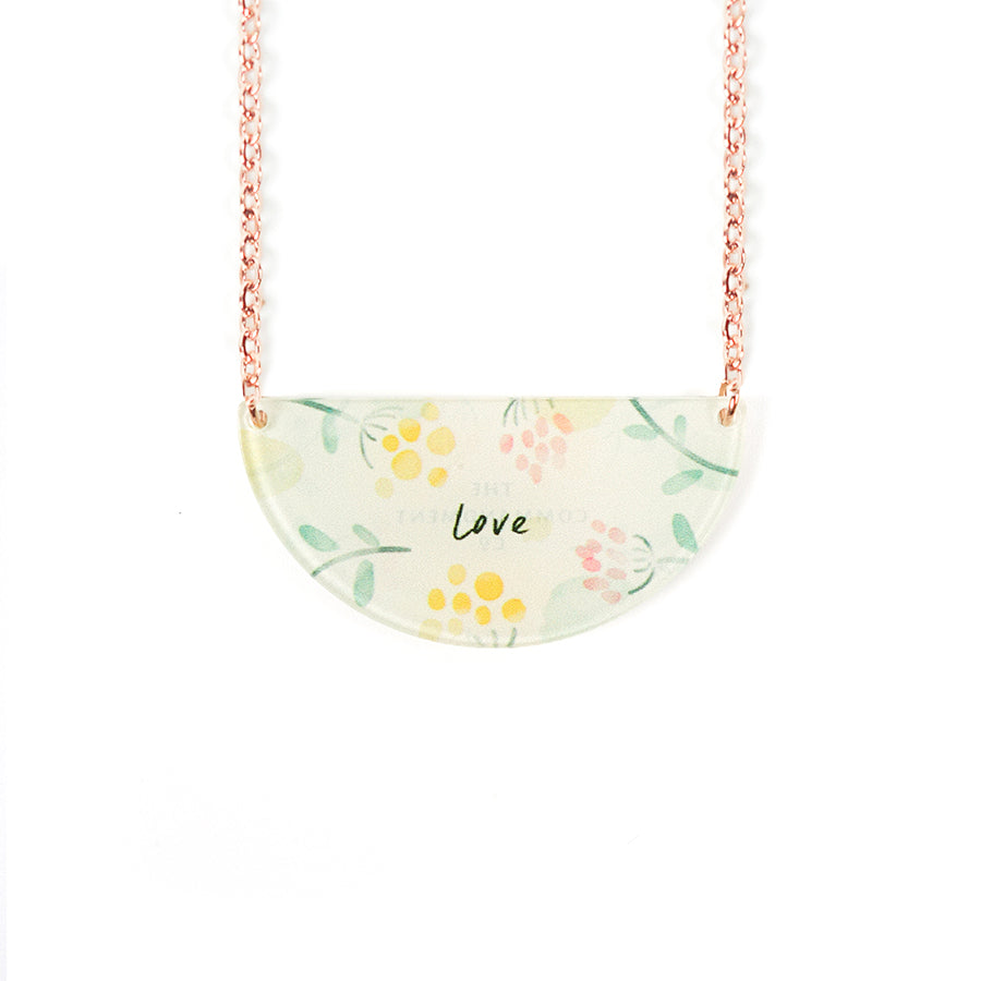 Acrylic semicircle white pendant with flower designs and bible verse 'love'. This necklace makes for unique gifts.