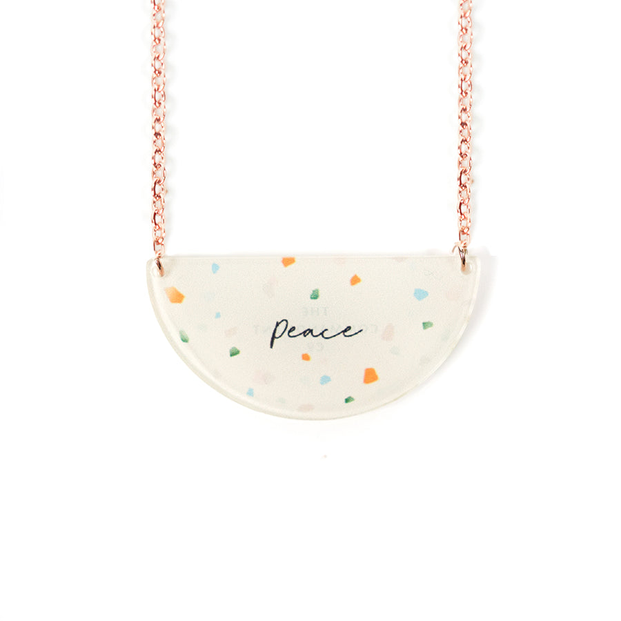 Acrylic semicircle off white pendant with terrazzo designs and bible verse 'peace'. This necklace makes for unique gifts.