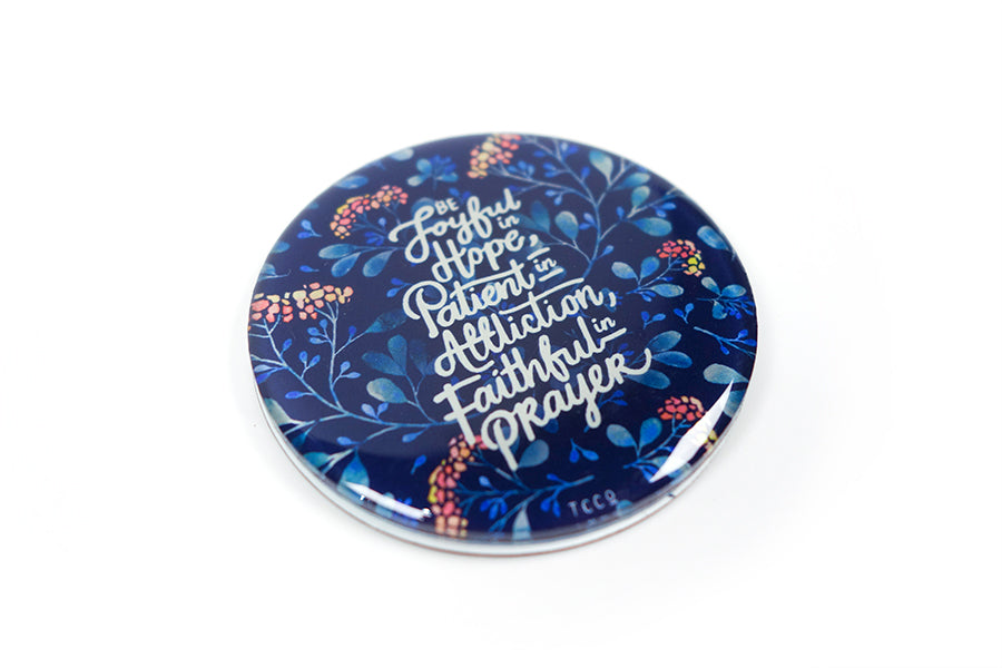 "Close up of 5.5 cm diameter circular Acrylic fridge magnet with bible verse ""Be joyful in Hope, patient in affliction, faithful in prayer"" on foliage background."