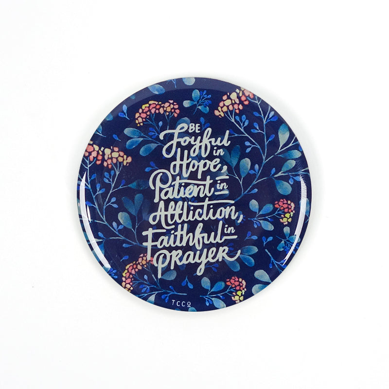 "5.5 cm diameter circular Acrylic fridge magnet with bible verse ""Be joyful in Hope, patient in affliction, faithful in prayer"" on foliage background."