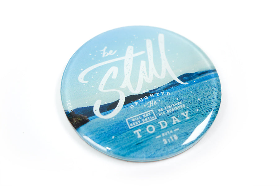 "Close up of 5.5 cm diameter circular Acrylic fridge magnet with bible verse ""Be Still"" on blue sea background."