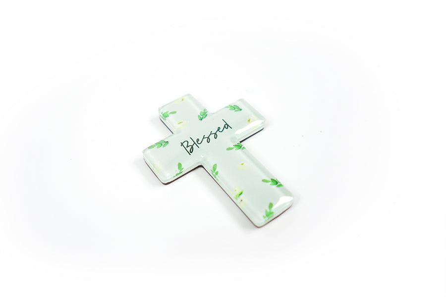 "Close up of 5.5 cm diameter pastel green cross Acrylic fridge magnet with verse ""blessed"" on garden foliage background."