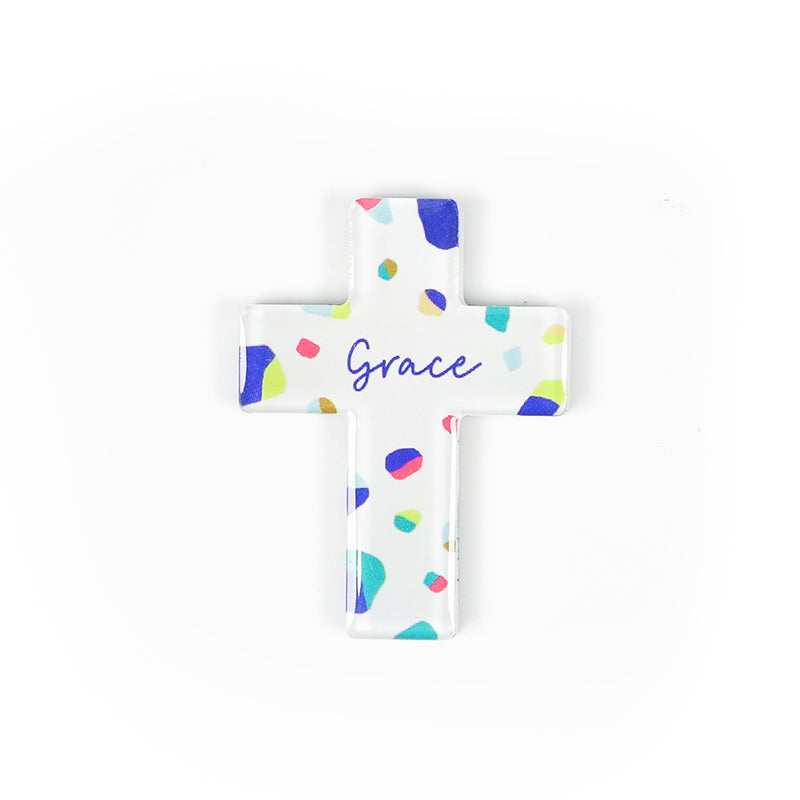 Cross acrylic magnet with colourful terrazzo design. And the encouraging message 'Grace' in blue.