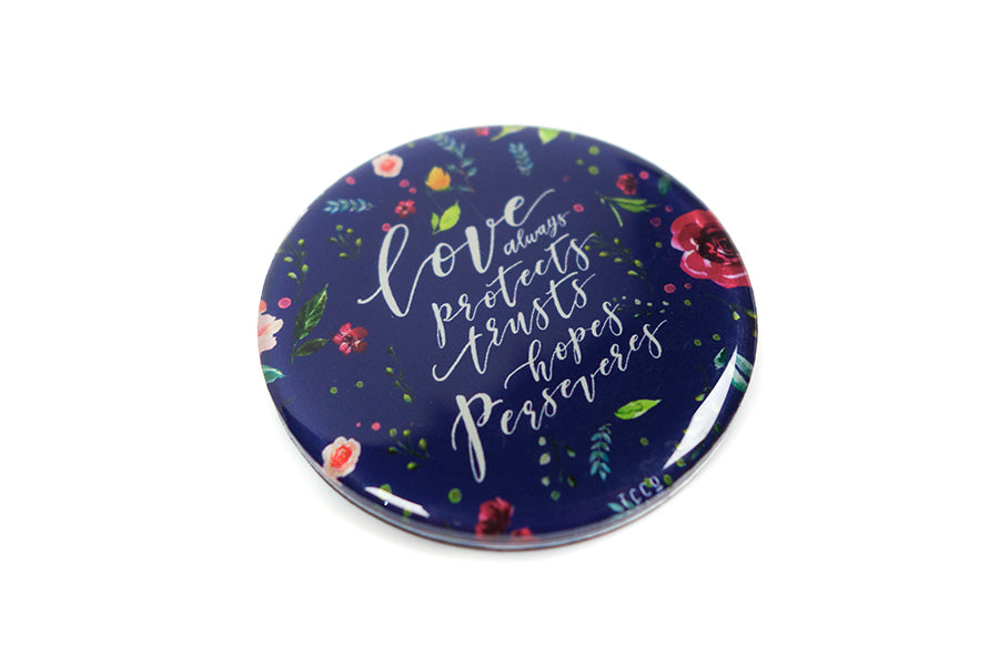 "Close up of 5.5 cm diameter circular Acrylic fridge magnet with bible verse ""Love always protects, trusts, hopes perseveres"" on foliage background."