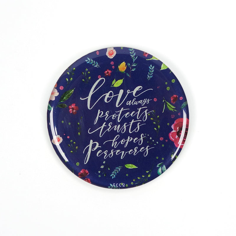"5.5 cm diameter circular Acrylic fridge magnet with bible verse ""Love always protects, trusts, hopes perseveres"" on foliage background."