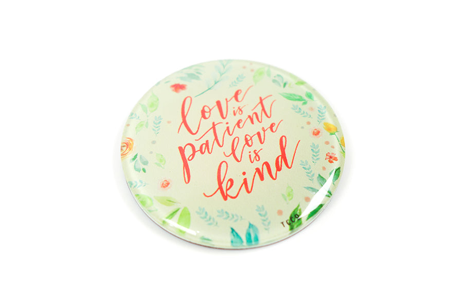 "Close up of 5.5 cm diameter circular Acrylic fridge magnet with bible verse ""Love is patient love is kind"" on foliage background."