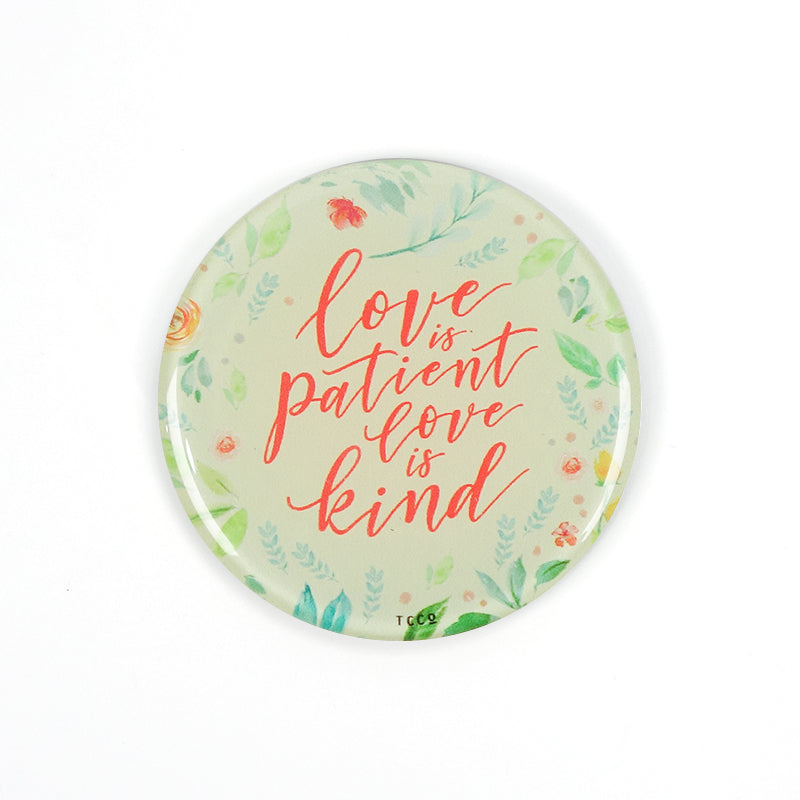 "5.5 cm diameter circular Acrylic fridge magnet with bible verse ""Love is patient love is kind"" on foliage background."