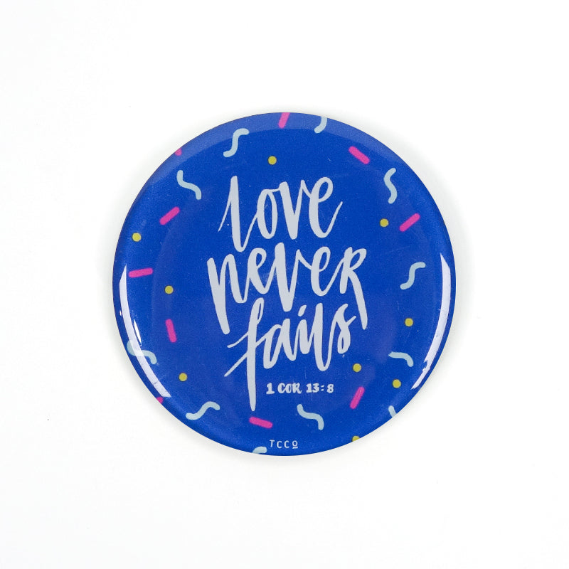 "5.5 cm diameter circular Acrylic fridge magnet with bible verse ""Love never fails"" on confetti background."