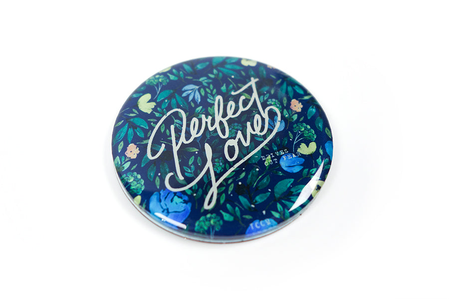 "Close up of 5.5 cm diameter circular Acrylic fridge magnet with bible verse ""Perfect Love casts out fear"" on foliage background."
