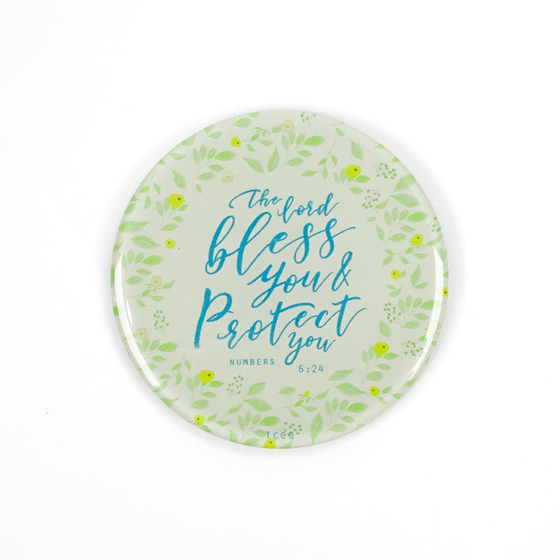 "5.5 cm diameter circular Acrylic fridge magnet with bible verse ""The Lord bless you and protect you"" on garden foliage background."