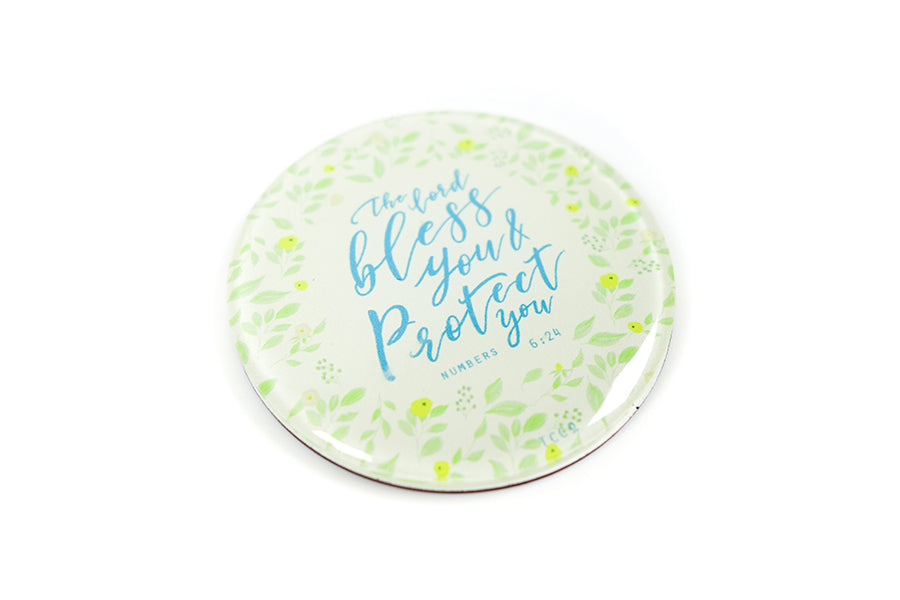 "Perspective photograph of 5.5 cm diameter circular Acrylic fridge magnet with bible verse ""The Lord bless you and protect you"" on garden foliage background."