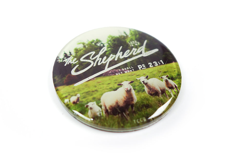"Close up of 5.5 cm diameter circular Acrylic fridge magnet with bible verse ""The Lord is my shepherd I shall not want"" on sheep and grassland background."