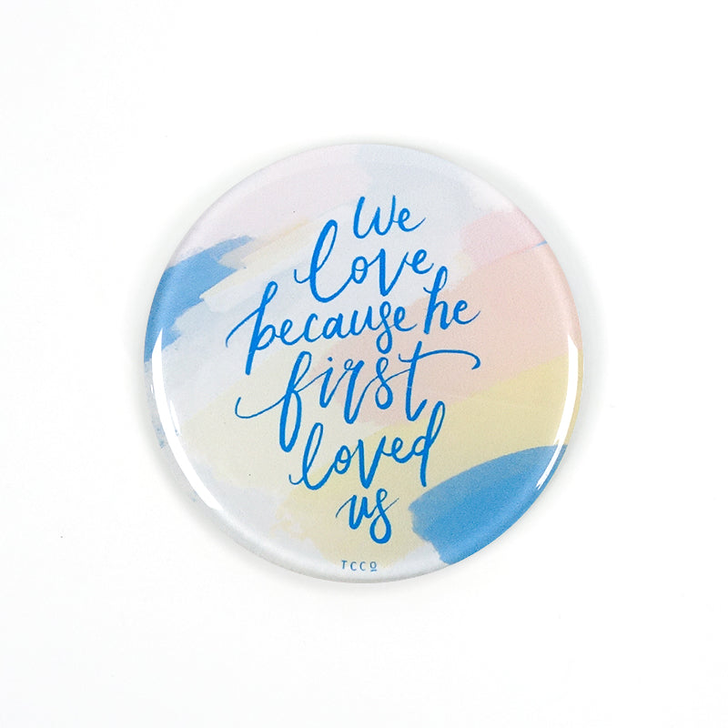 "5.5 cm diameter circular Acrylic fridge magnet with bible verse ""We love because he first loved us"" on brush swatches background."