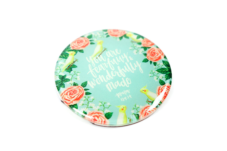 "Close up of 5.5 cm diameter circular Acrylic fridge magnet with bible verse ""You are fearfully and wonderfully made"" on songbird and flowers background."